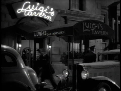 vídeos de stock, filmes e b-roll de 1940s ws patrons coming and going from luigi's tavern as a valet paces near the street / united states - mordomo equipe doméstica
