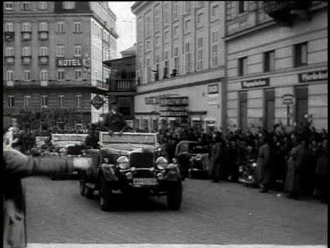 1940s ts people cheering adolf hitler as he is driven down an austrian street / austria - hakenkreuzfahne stock-videos und b-roll-filmmaterial