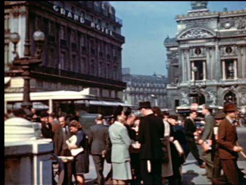 1940s PAN people going down stairs of Opera Metro entrance / traffic + Opera Garnier in background / Paris, France