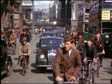 vídeos de stock, filmes e b-roll de 1940s people riding bicycles, cars + double decker bus in heavy traffic on city street / dublin - lugar genérico