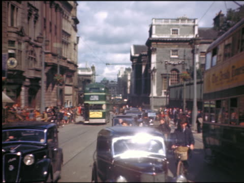vidéos et rushes de 1940s people riding bicycles, cars + double decker buses in heavy traffic on city street / dublin - irlande