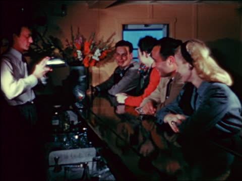 vidéos et rushes de 1940s people sitting at bar talking as bartender mixes drink in shaker / travelogue - shaker