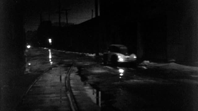 a 1940s police car travels down a wet, deserted street at night. - 1940 1949 stock-videos und b-roll-filmmaterial