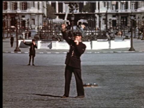 vídeos de stock e filmes b-roll de 1940s policeman signaling traffic with stick / other policeman + fountain in background / paris, france - maça