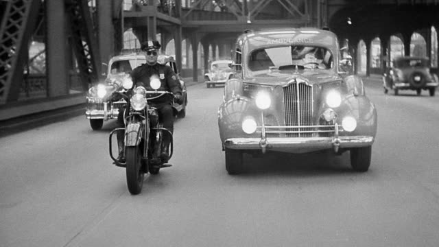 b/w 1940s rear car point of view driving on bridge with motorcycle officer escorting ambulance - moving process plate stock videos & royalty-free footage
