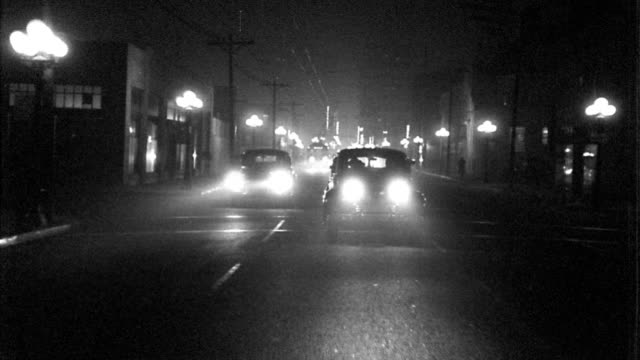 b/w 1940s rear car point of view driving + turning on city streets at night with cars behind / los angeles - moving process plate stock videos & royalty-free footage