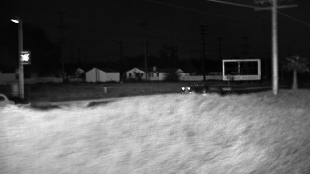 B/W 1940s REAR SIDE car/train point of view wide shot driving next to suburban road at night / Los Angeles