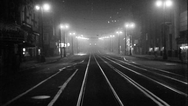 B/W 1940s REAR trolley/car point of view driving over tracks on city street at night / Los Angeles