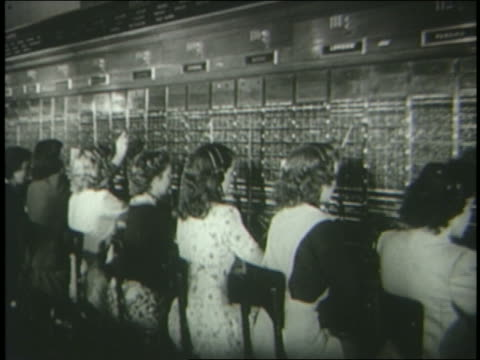 b/w 1940s rear view female telephone operators working at switchboard - 電話交換機点の映像素材/bロール