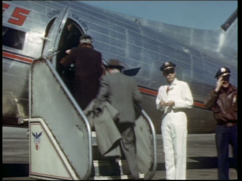 1940s rear view of people boarding airplane outdoors as crew stands by - flugpassagier stock-videos und b-roll-filmmaterial
