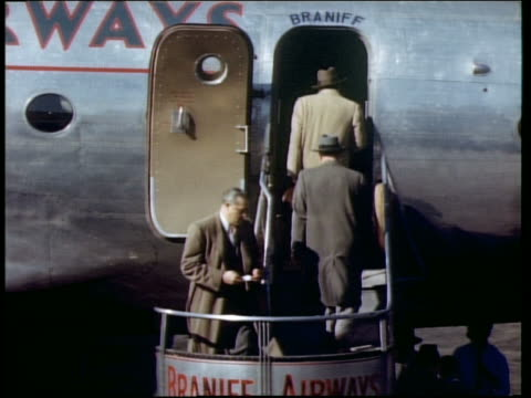 1940s rear view of people boarding braniff airways airplane outdoors using curved stairway - 搭乗者点の映像素材/bロール
