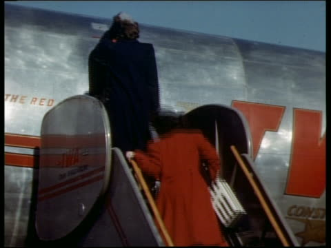 1940s rear view of stewardesses + ground crew member boarding twa airplane outdoors - twa video stock e b–roll
