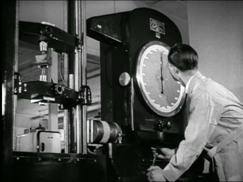 stockvideo's en b-roll-footage met b/w 1940s rear view scientist looking at large meter in laboratory / industrial - 1940