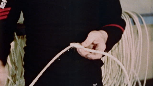1940s sailor demonstrating how to tie knot - marinaio video stock e b–roll