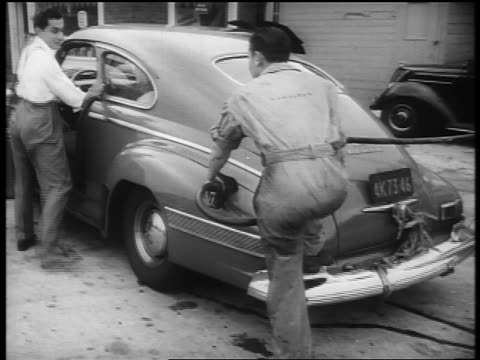b/w 1940s service station attendant pumping gas in car of excited man / newsreel - gas station attendant stock videos and b-roll footage