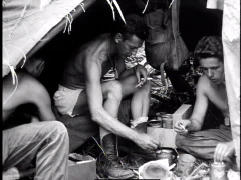 1940s ms shirtless soldiers sitting under shelter at makeshift camp eating / europe - shirtless stock videos & royalty-free footage