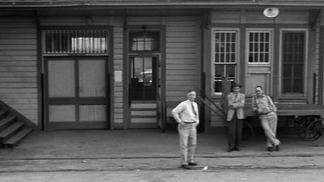 b/w 1940s side train point of view passing through small town with train station + streets / richfield, ca - inquadratura da un treno video stock e b–roll