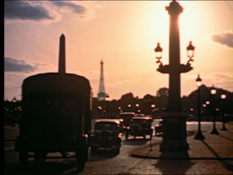 1940s silhouetted traffic + Obelisk in Place de la Concorde at sunset / Eiffel Tower in background / Paris