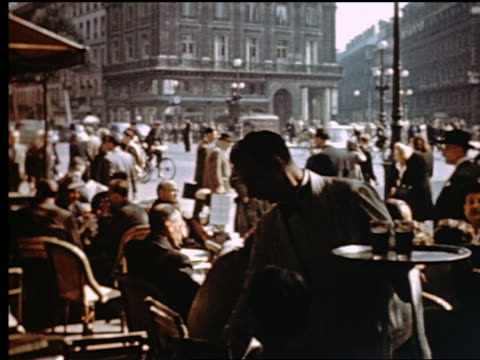 1940s silhouetted waiter serving drinks at sidewalk cafe / people + traffic in background / paris - 1940 stock videos & royalty-free footage