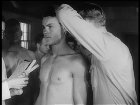 B/W 1940s soldier checks ears + throat of shirtless new recruit