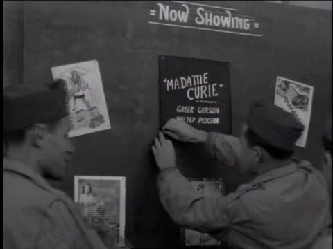 1940s MS soldier tacking an advertisement to a board that says Now Showing / European Theater of Operations
