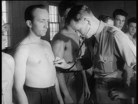 vídeos de stock e filmes b-roll de b/w 1940s soldier with stethoscope listens to heart of shirtless new recruit - estetoscópio