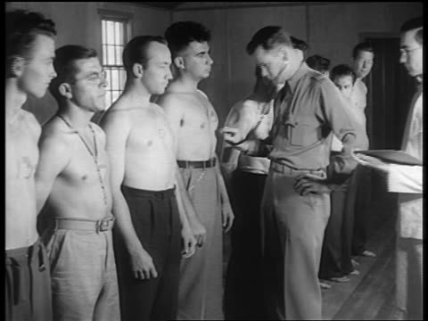 stockvideo's en b-roll-footage met b/w 1940s soldier with stethoscope listens to hearts of shirtless new recruits - rekruut