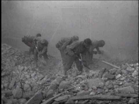 1940s soldiers digging in rubble with shovels / europe - rubble stock-videos und b-roll-filmmaterial