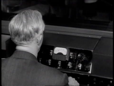 1940s TU technician operating the sound booth and conductor leading the band during an Andrews Sisters recording session / United States
