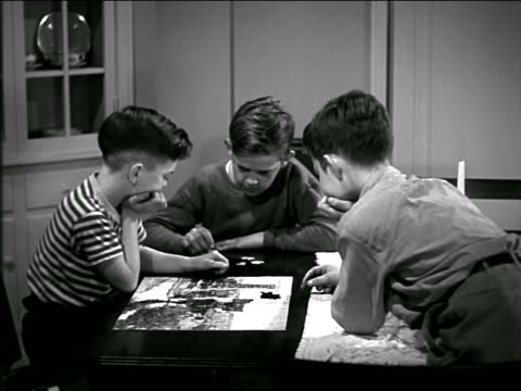 b/w 1940s three boys playing with jigsaw puzzle at table - jigsaw puzzle stock videos & royalty-free footage