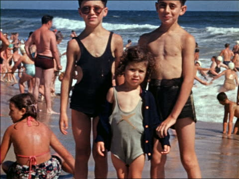 vidéos et rushes de 1940s three children in swimsuits posing on beach / one boy wearing sunglasses / home movie - brother