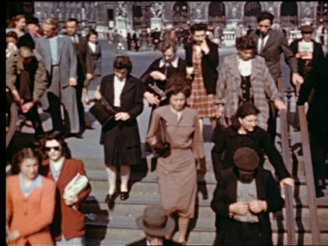 1940s tilt up from people going down stairs of Metro entrance to Opera Garnier in background / Paris