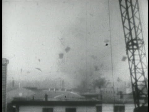 B/W 1940s tornado tearing up roofs of buildings in distance