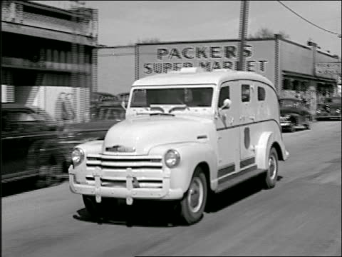 b/w 1940s tracking shot armored car driving on town street - armored truck stock videos and b-roll footage