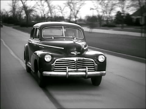B/W 1940s tracking shot car driving on suburban street