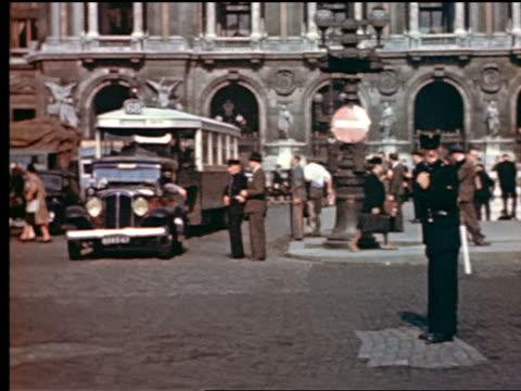 1940s pan traffic, policemen + people walking in place de l'opera / paris, france - place de l'opera stock videos and b-roll footage