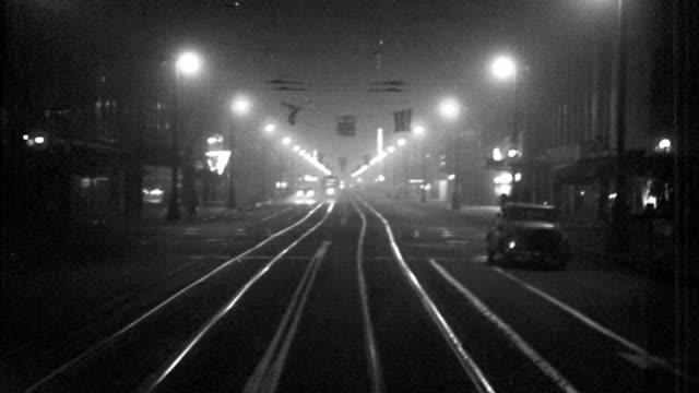 vídeos de stock, filmes e b-roll de b/w 1940s trolley point of view on city street at night with trolley coming in opposite direction / los angeles - ponto de vista de bonde