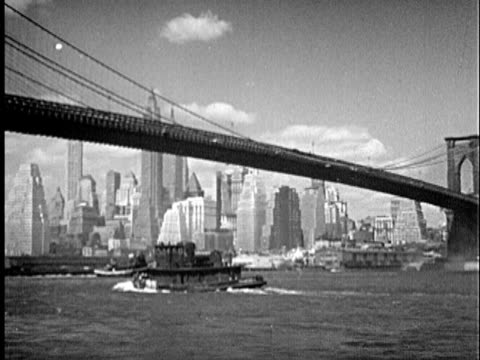 b/w ws 1940s tugboat and steamship passing underneath brooklyn bridge, new york city skyline in background / new york city, new york - 1945 stock videos and b-roll footage