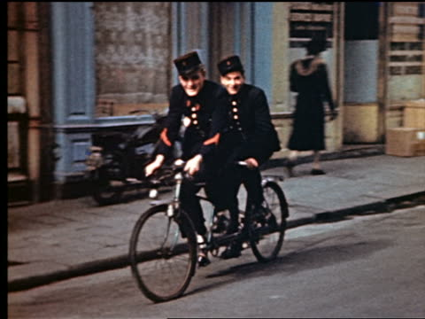 1940s PAN two policemen riding tandem bicycle on street / people on sidewalk in background / Paris, France