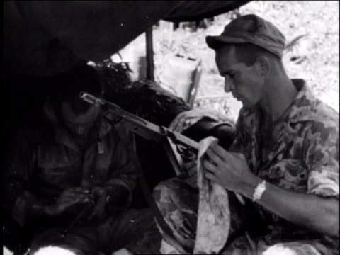 1940s ms two soldiers sitting cleaning rifles under shelter at makeshift camp / europe - gewehr stock-videos und b-roll-filmmaterial