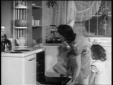 b/w 1940s two young girls watching woman open oven + remove cakes in kitchen - stay at home mother stock videos & royalty-free footage