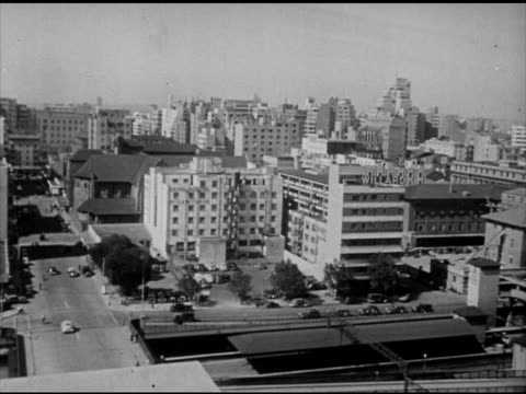 union of south africa vs metropolitan city buildings european native south africans walking city streets double decker trolley bus bg traffic shops... - trolley bus stock videos & royalty-free footage