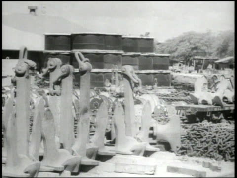 stockpile of various u.s. naval yard equipment, including oil drums, anchors, chains , incomplete tanks in tank yard, incomplete landing crafts in... - stahlfass stock-videos und b-roll-filmmaterial