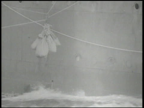 UNITED STATES NAVY VS US Navy cargo transport ships at sea mailbags going across zip line between ships seamen on deck calling out names distributing...