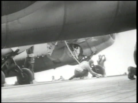 UNITED STATES NAVY VS US Navy fighter planes starting engines on aircraft carrier deck propellers spinning crew checking wheels locking into wings...