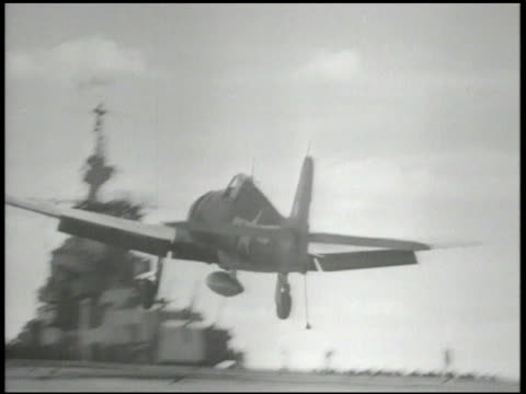 navy signal officer signaling on aircraft carrier deck, fighting airplane landing on deck runway, crew unhooking arresting gear from tailhook, crew... - war stock-videos und b-roll-filmmaterial