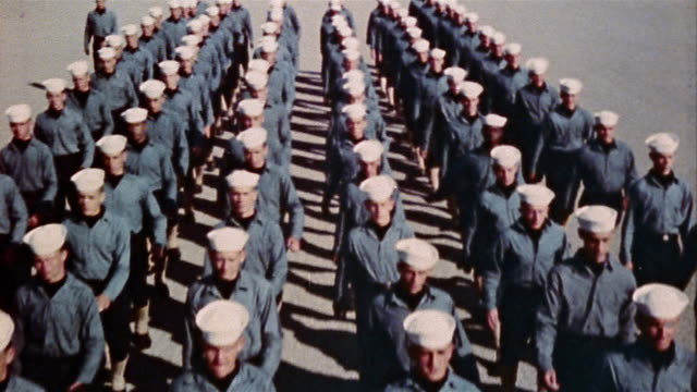 1940s US Navy officer leading recruits in marching drill at naval training center