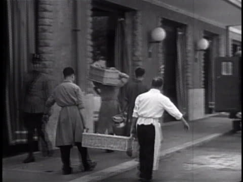 VATICAN CITY SUPPLIES Males carrying food baskets milk containers into shop loading truck INT Apothecary w/ people shopping Imported goods food