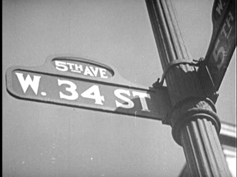 b/w cu la 1940s 'w. 34 street' street sign at 'fifth ave' / new york city, new york - prelinger archive stock videos & royalty-free footage