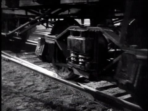 1940s zo wheels of train traveling on track, brakeman with lantern jumping off as train slows - 車輪点の映像素材/bロール